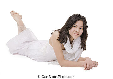Young teenage girl in white dress lying down, isolated
