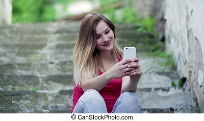 Young teenage girl sitting outdoors in town, using...