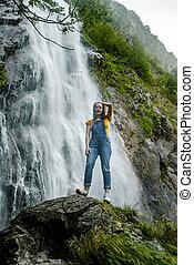 Young teenage girl standing on the big stone near waterfall