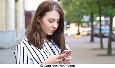 Young teenage girl texting outdoors on phone at sunset, smiling