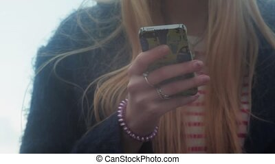 Young teenage girl texting outdoors on phone