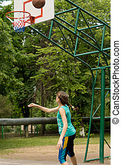 Young teenage girl throwing a basketball
