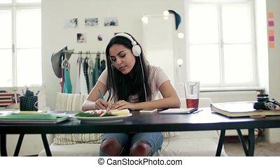 Young teenage girl with headphones sitting indoors,...