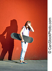 teenage girl with skateboard in the street