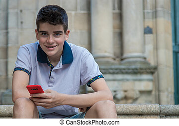 young teenage man with mobile phone outdoors