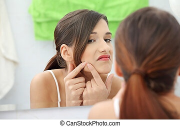 Young teenage woman with pimple on her face