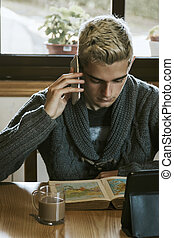 young teenager at home studying with mobile phone