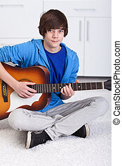 Young teenager boy playing the guitar