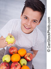 Young teenager boy sitting on the floor with a plate of fresh fruit