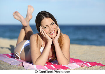 Young teenager girl on the beach looking at camera with the...