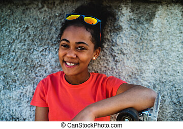 Young teenager girl sitting outdoors in city, leaning on concrete wall.