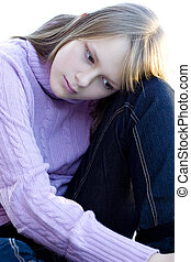 Young teenager girl sitting with her knee bent in sad...
