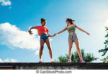 Young teenager girls friends outdoors in city, standing on concrete wall.