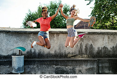 Young teenager girls friends with skateboards outdoors in city, jumping.