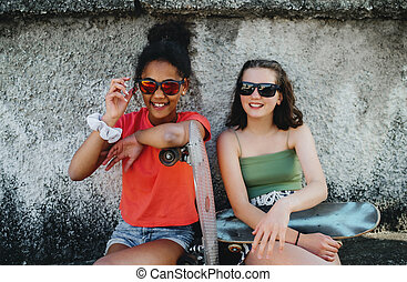 Young teenager girls friends with skateboards outdoors in city, sitting.