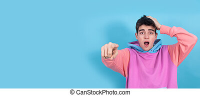 young teenager or student boy with expression of surprise or admiration pointing by hand