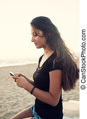 Young teenager while using the smartphone on the beach