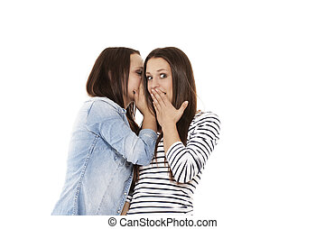 young teenager whispering at her surprised sister on white background
