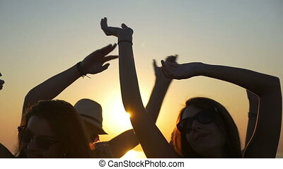 Young teenagers waving their hands in the air at sunset