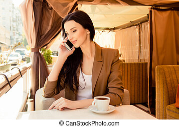 Young tender woman talking on phone at dinner with cup of coffee