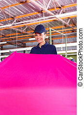 young textile factory worker holding large fabric