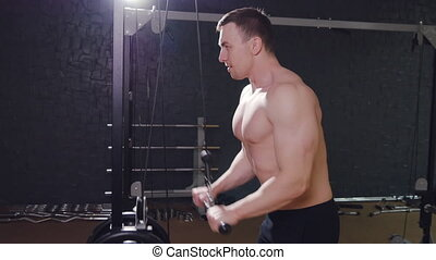 Young The man trains triceps in the gym