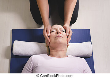 Young therapist doing reiki therapy to senior woman -...