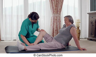 Young therapist exercising with older female patient