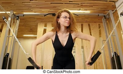 Young thin woman doing fitness in the gym. Mid shot