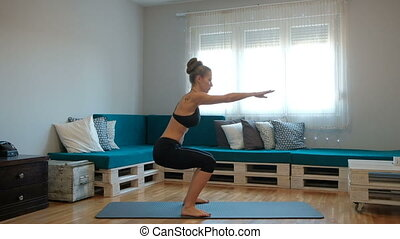 Young thin woman in training suit do exercise on mat indoor.