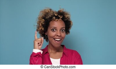 Young thinking african woman having idea pointing finger up ...