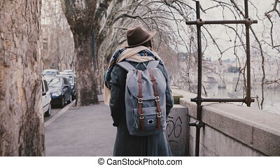 Young thoughtful local girl with backpack in warm clothes...