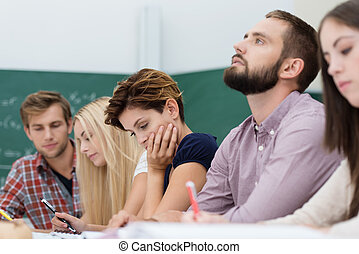 Young thoughtful male university student sitting in a group...