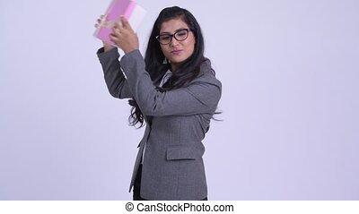 Young thoughtful Persian businesswoman shaking gift box -...