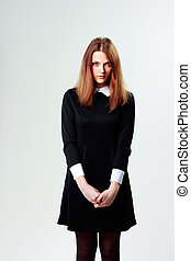 Young thoughtful woman in black dress on gray background