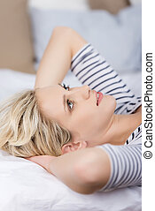 Young Thoughtful Woman Lying On Bed