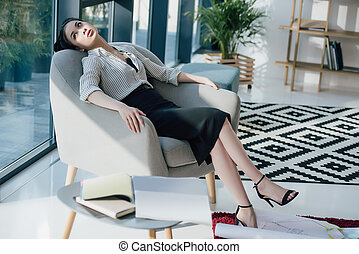 Young tired asian businesswoman sitting in chair and looking at window