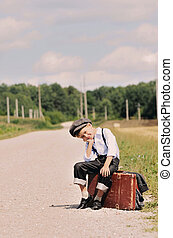 young tired traveller sitting on the road
