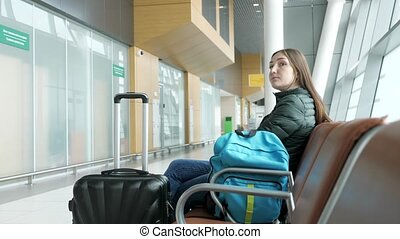 Young tired woman is waiting her flight in airport sitting in hall.