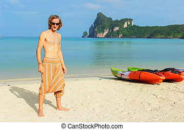 young topless man standing in front of a row  Kayaks canoes boats on the PhiPhi Don beach in Thailand