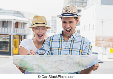 Young tourist couple consulting the map with magnifying ...