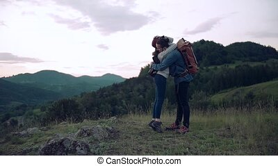 Young tourist couple travellers with backpacks hiking in nature, hugging.