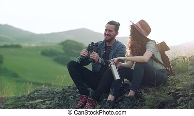 Young tourist couple travellers with binoculars hiking in nature, sitting and resting.