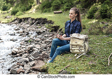 Young tourist girl sitting on the shore of a mountain river and looking at a beautiful landscape. Hiking woman with backpack relaxing