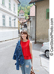 Young tourist girl walks by street A small town in the mountains of Slovenia, Europe. Shabby old houses facades, and roofs.