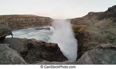 Young tourist man taking photos of beautiful Gullfoss waterfall in Iceland. Traveling male exploring the new place.