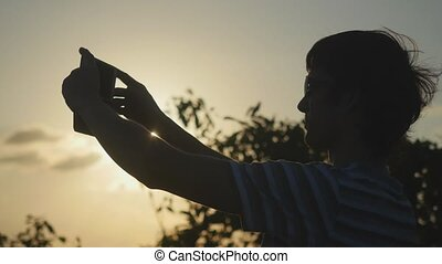 Young tourist man wearing sunglasses taking picture of sunset on top of the mountain.