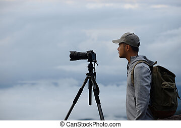Young tourist man with backpack looking through camera at the sea of fog