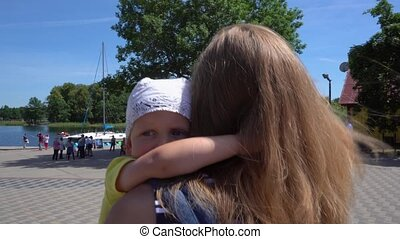 Young tourist mother carries a tired baby boy near lake....