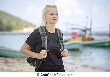 Young tourist of a blonde girl with backpack on the beach with pleasure looking at a beautiful sea landscape